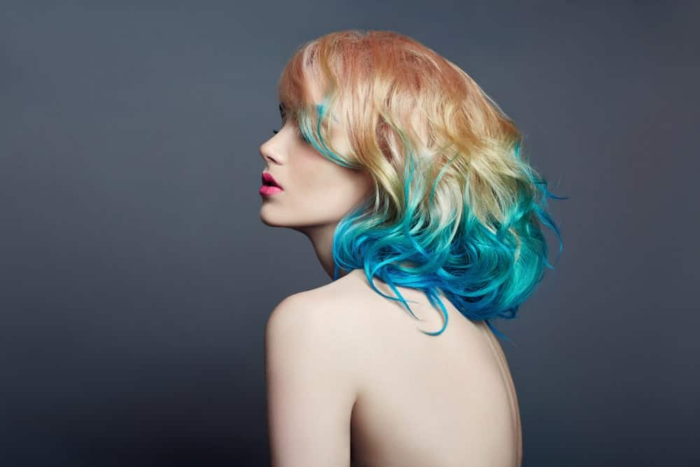 This mermaid-style hair look shows off a variety of jewel-blue colors, including shades of bright turquoise and sapphire. Although most of the color is situated on the bottom half of her hair, tendrils of the blue color have bled up. The model's hair has been given further dimension by coloring her roots a strawberry blonde, which graduates to a lighter blonde before it meets the blue.