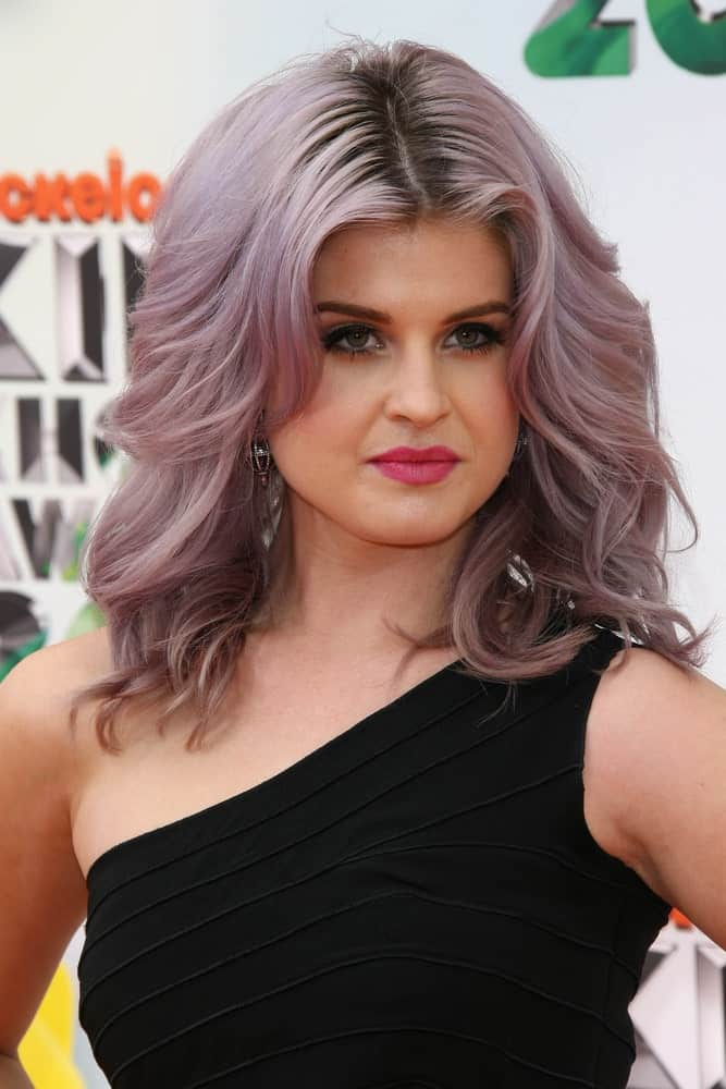 Kelly Osbourne's pompous hairstyle for women with gray hair consists of a prominent balayage and a tint of violet in the upper tresses. A clean center-part has been followed by voluminous waves doused with loads of hairspray to create this lively, forever-wind-blown hairstyle.
