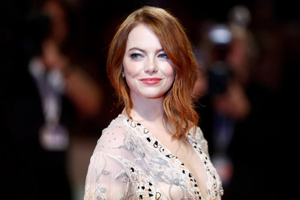 Although Emma Stone is a natural blonde, the actress is more often seen with her hair a brilliant shade of Auburn. In fact, many people don't even know red is not Stone's natural hair color. However, with her inspiring fashion sense, Stone now owns the color. Here, the actress is sporting side-parted loose asymmetrical waves with the rest of her hair pulled back in a bun. The look is both chic and modern.