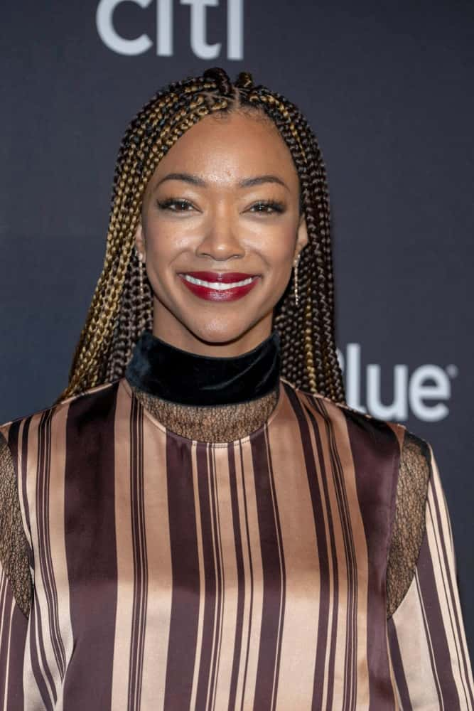 "Another beautiful celebrity, Sonequa Martin-Green, was seen rocking Fulani braids at the 2019 Paley Fest. The actress styled her Fulani braids in a minimalistic way. Half her locks remained dark brown while the other half was colored a beautiful burnished gold. The ""Star Trek: Discovery"" actress chose to forego the traditional shells, beads, and thread decorations in her cascading hair, preferring to show off the beautifully two-toned dangling length of her hair."