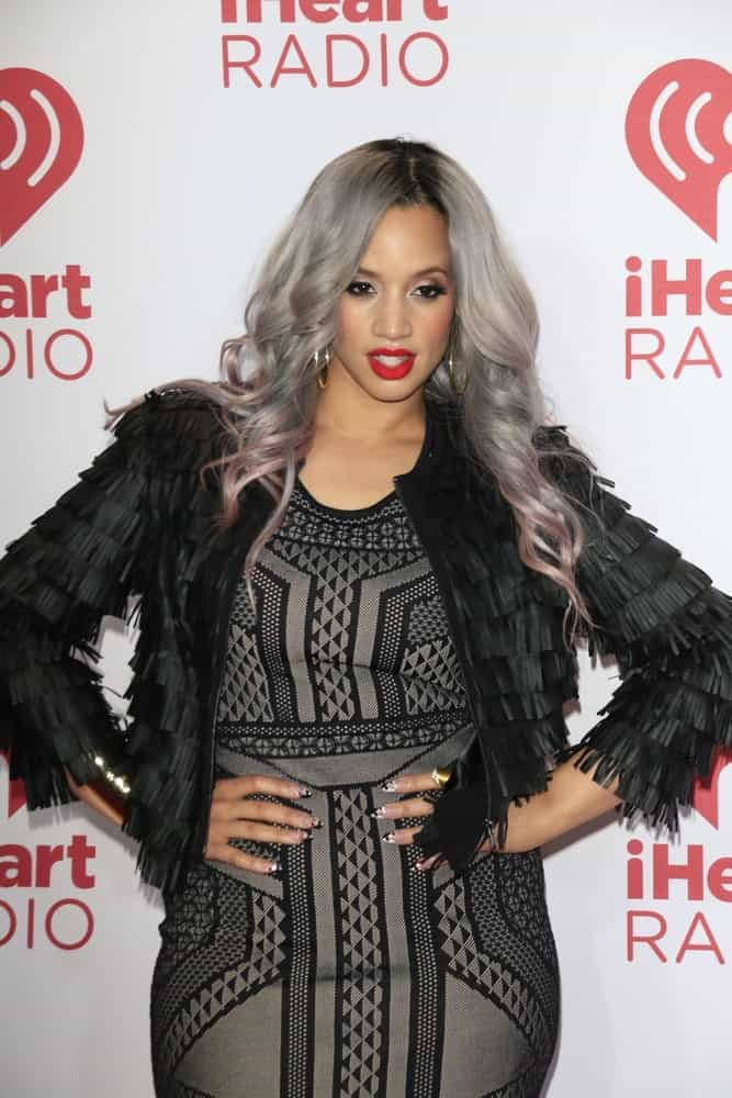 While she wore her dyed gray hair in a ponytail with bangs at the ALMA Awards in Pasadena, CA, here we see Dascha Polanco flaunting her new hair color by simply wearing them in a down-style. After neatly center-parting her hair, she tossed them in front of her shoulders to let the gray glory shine up front. The ends have been slightly tousled to add more volume and texture whereas the light mauve lowlights further up her glam game.