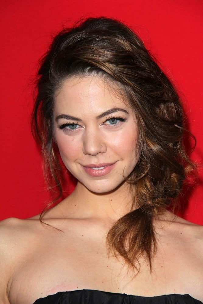 Analeigh Tipton's loose hairstyle is so messy that it's hard to notice that there is a three-strand braid incorporated into it. Tossing her hair to one side, the actress has formed it into an extremely loose plait but note that despite the chaotic style, she still looks pretty attractive.