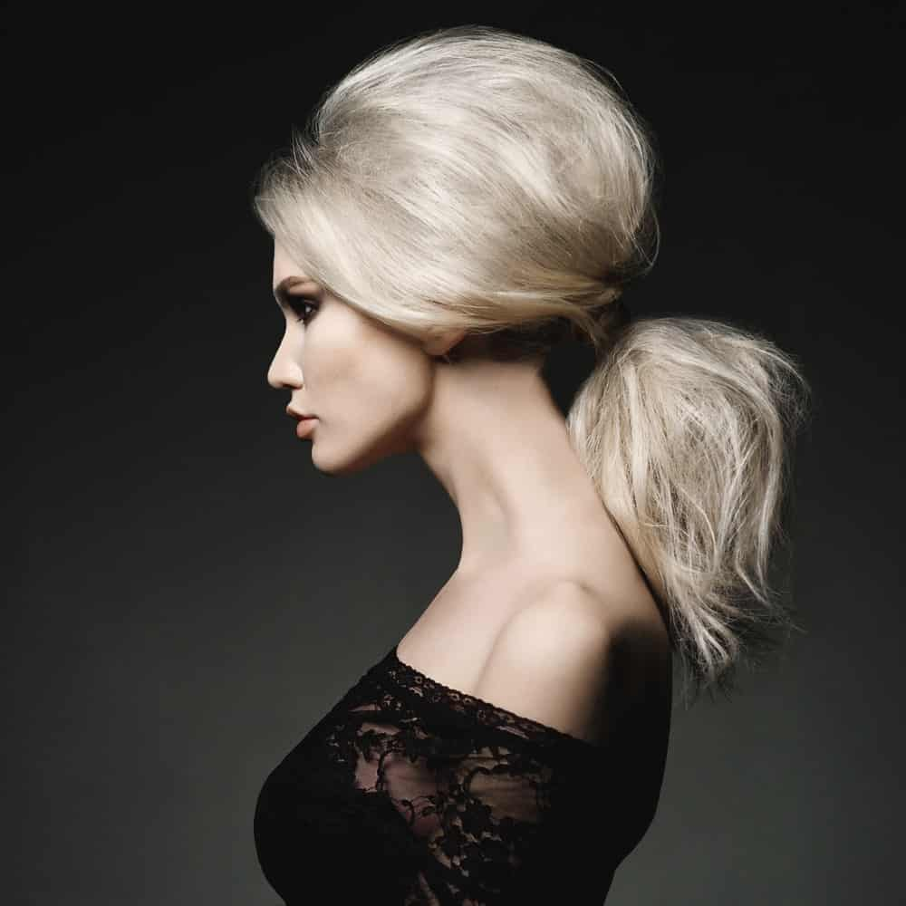 Do you want to rock an elegant ponytail? Get it done with a Brigitte Bardot-style beehive. Backcomb the back of your hair so that it makes a full and elegant bouffant. Then apply a lot of texturizing spray to your locks so that they appear fuller. Finally, tie your hair into a low ponytail for a super elegant look!