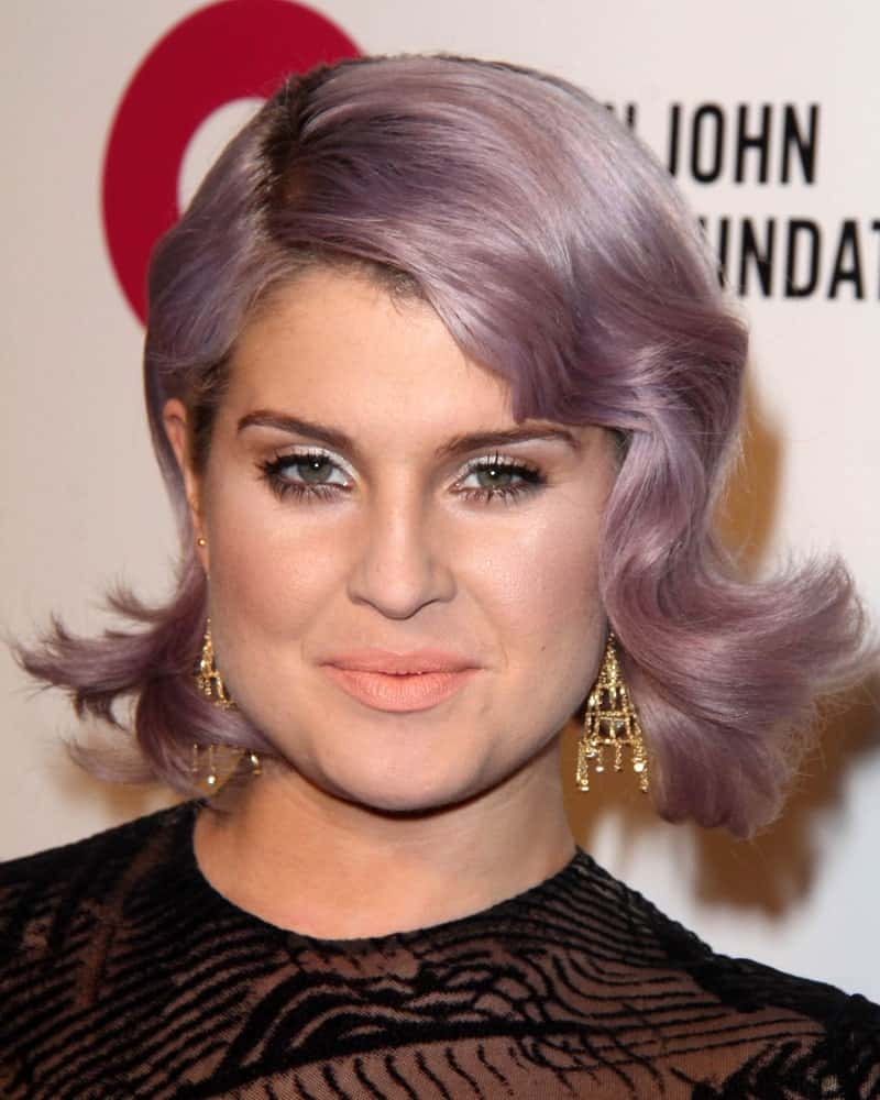 Here we see Kelly Osbourne flaunting her iconic purplish-gray hair with sheer flamboyance and still looking really classy despite the ostentatiousness. Her bob cut hair has been twisted and tousled unusually to create this a-symmetrical hairstyle that is overflowing with gorgeousness and magnificence.