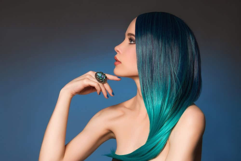 Jewel tones hair colors are trending with the masses these days, Here, this model sports a beautiful ombre which starts with a very dark green emerald tone at the top and graduates to lighter jade green color from the middle to the end. This is a perfect mermaid hair look.
