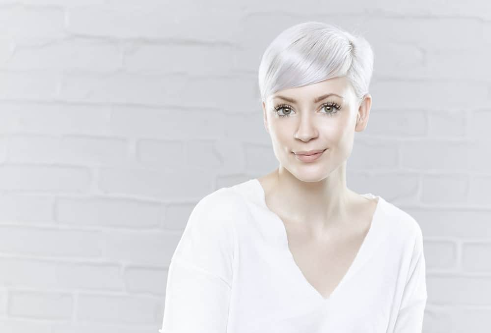 Here is an example of another super-short hairstyle; however, this one features longer hair in the front that is styled in adorable slanting bangs across the forehead. The shiny white hair puts the wow factor in this style. This is a great look for those who want to highlight their eyes and jawbone. The side swept bangs with a pixie cut also takes years off one's face.