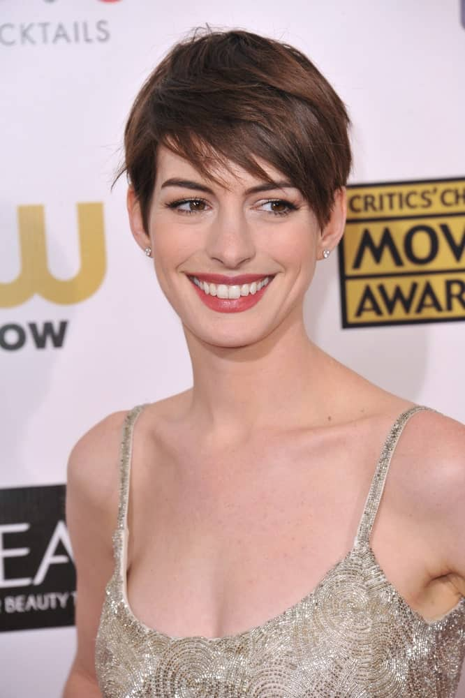 Looking for a really short side-swept haircut? Take a look at the Hollywood charmer, Anne Hathaway's funky and fashionable pixie cut adorned with uneven, side-swept and airy-separated bangs.