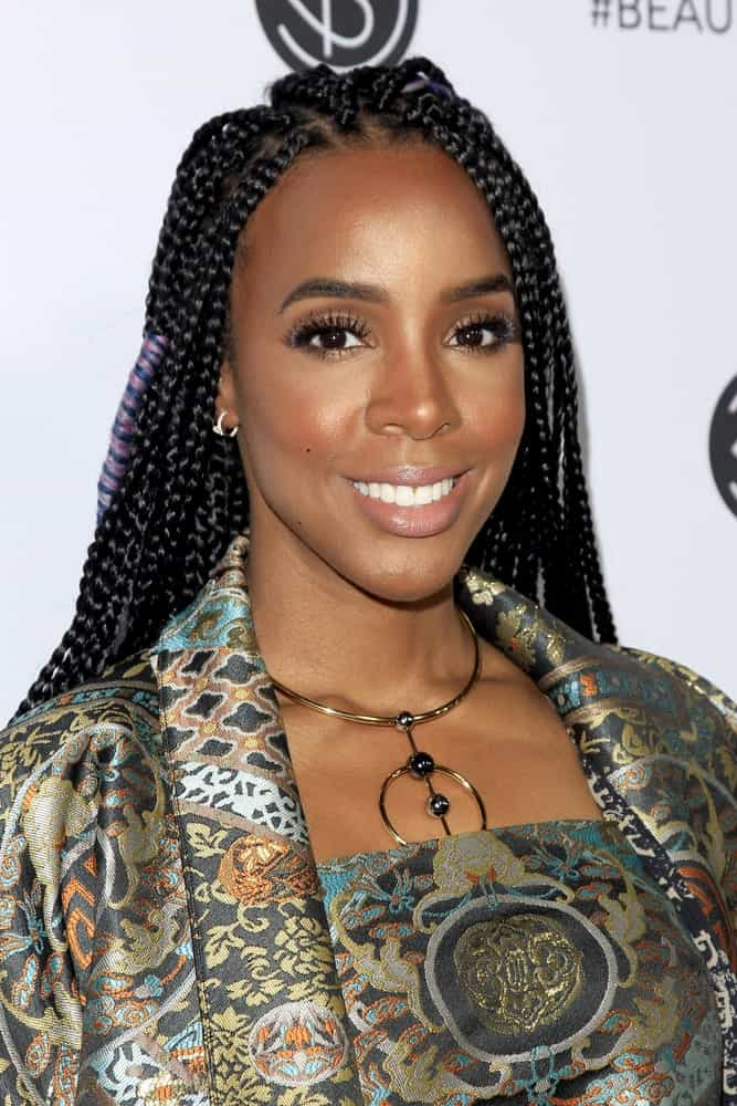 """Kelly Rowland paired her colorfully-printed silk dress with Fulani braids at the 5thAnnual Beautycon Festival in 2017. The former member of """"Destiny's Child"""" kept her long hair pushed back from her face with the help of multitudes of braids. Most of her braids remained unadorned but she wrapped lilac and blue threads around a few of her side braids for some beautiful accent in contrasting color. This style of braid looks perfect on her."""