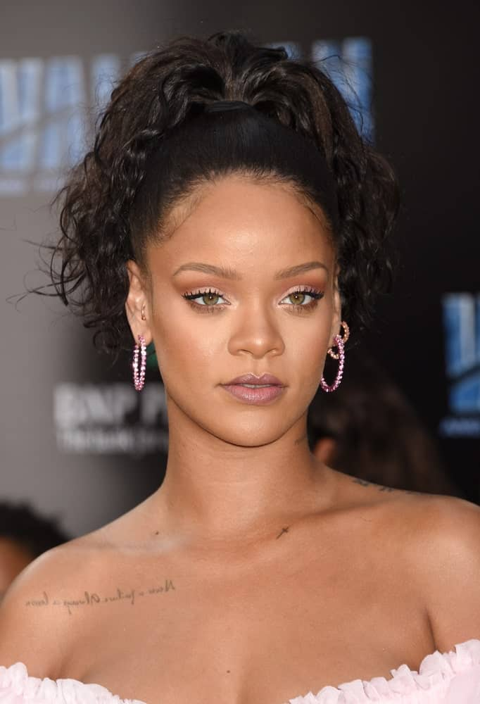 Rihanna's high fountain-style ponytail is a smart way to let curly hair take center stage. The gorgeous jet-black loose curls falling onto her shoulders make her look super stylish besides emphasizing her face structure even more.