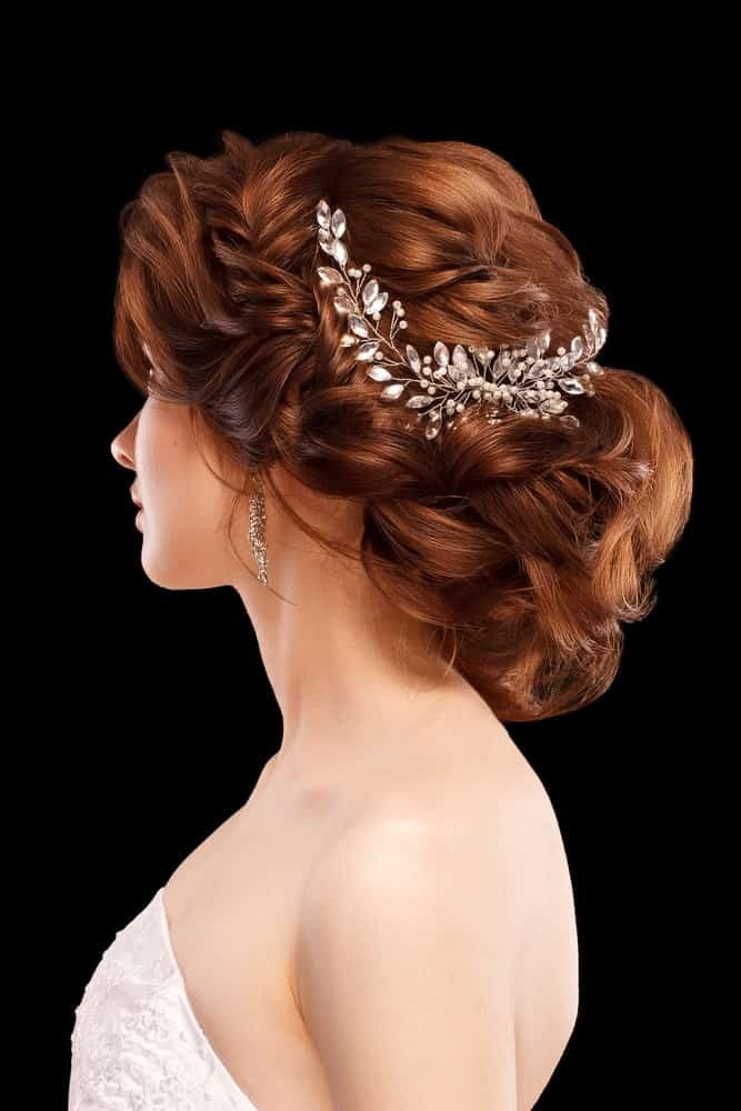 Work of an expert hairstylist, this glamorous wedding hairstyle is truly exceptional with all the intricacies involved. There's a fish-plait at the side that combined with the thick regular braids before being rounded into a fluffy bun at the back.