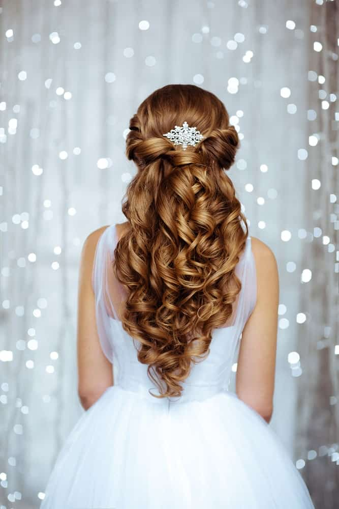 This fancy curtain of red is good for brides who have extra lengthy red or dark brunette hair. Curl them heavily before securing two side-strands at the back with a silver comb. This elaborate hairstyle is bound to stun all guests in attendance.
