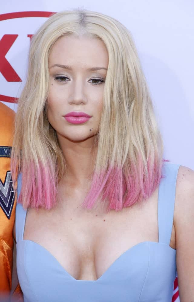 Iggy Azalea has experimented with a lot of hairstyles and this particular multi-colored hairstyle is one of her best looks. The rapper kept the top of her naturally blonde but dip-dyed the ends with a millennium pink color. Not only does the style brighten up her face but it also makes her look younger. Shocking Pink and Red Style
