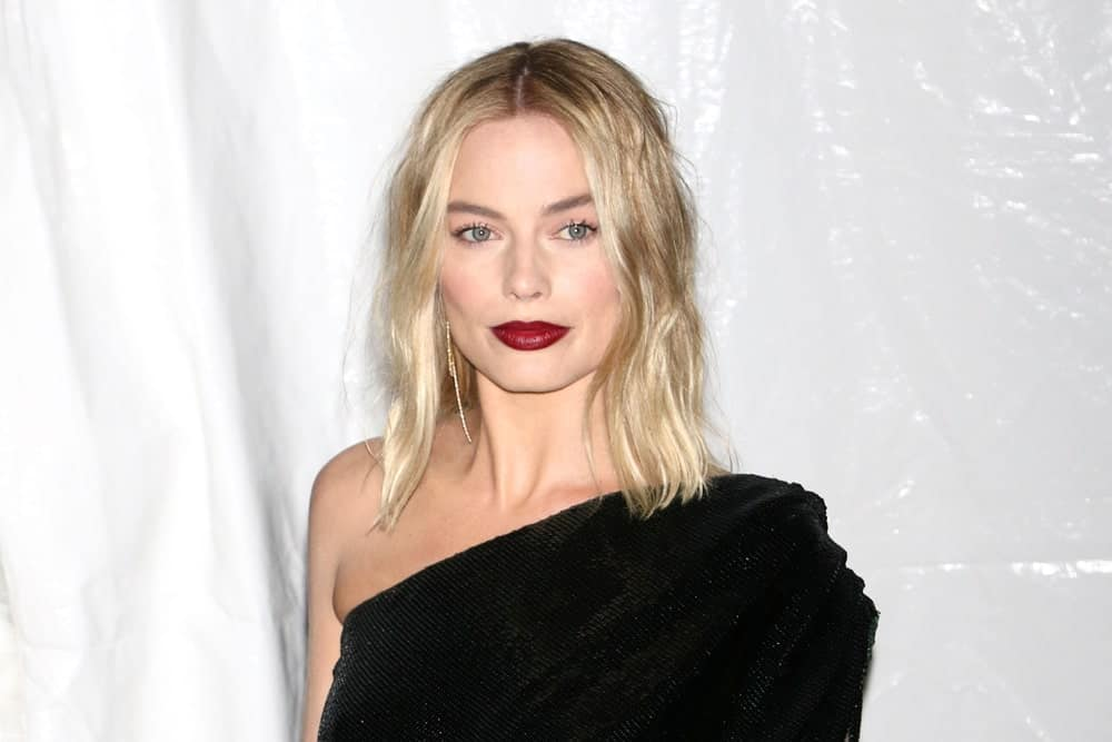 "Margot Robbie seems to be giving out some serious grunge, rock and roll vibes here. The ""I, Tonya"" actress has rocked the blonde look for a long time but she changes her hairstyles like a chameleon. The actress parted her hair messily in the middle and let her pale blonde hair fall to her shoulders. She added a volumizing product to give her hair a slightly crimped and shaggy look, which goes perfectly with her black outfit and dark cherry lipstick."