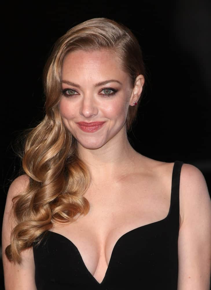 Amanda Seyfried's side-swept hairstyle comprises of a bunch of big and bouncy curls all rested on one shoulder. All it takes is a few minutes of curling, and you have an elegant hairstyle with minimal effort.