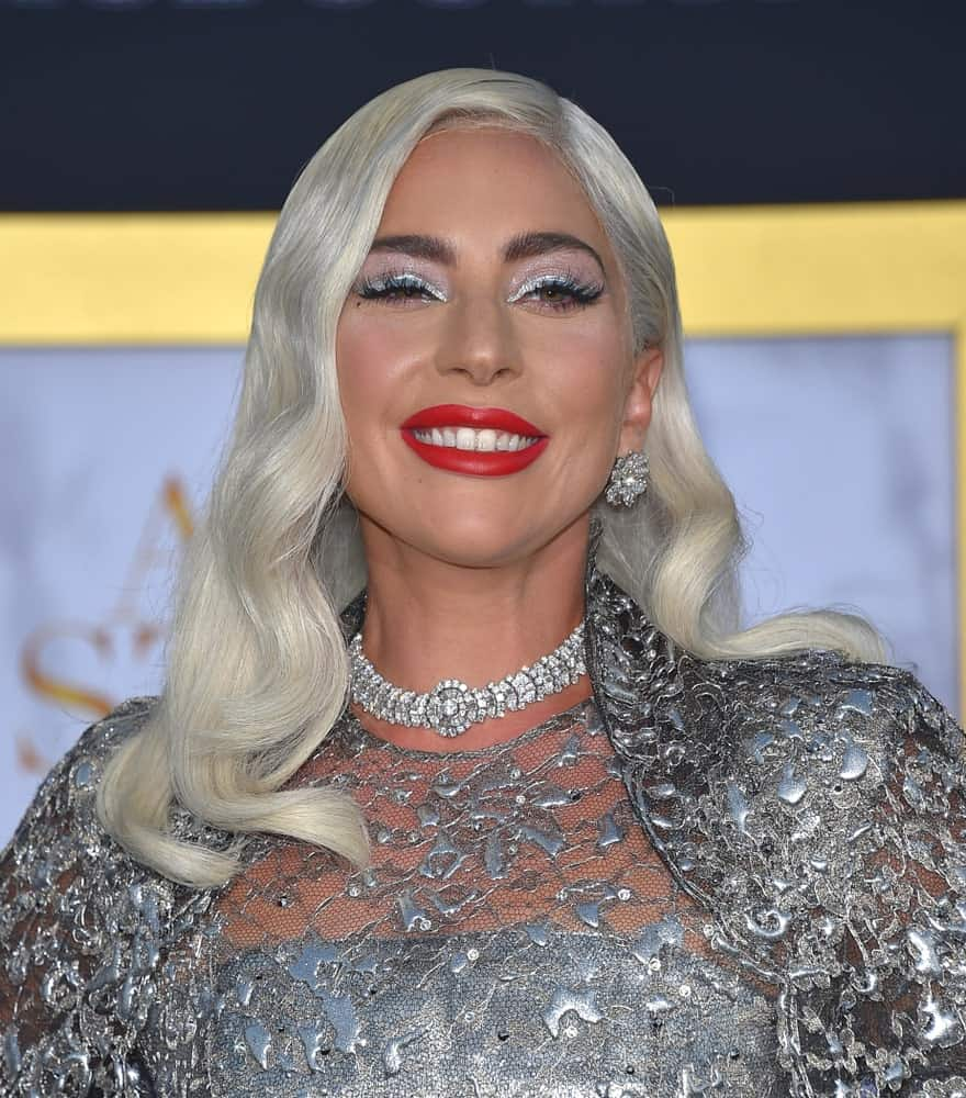 The all-time favorite singer, Lady Gaga, deliberately went gray, or to be more precise, ash white on purpose and arrived at the Premiere of her latest film, A Star is Born, while sporting the new hair shade. Needless to say, she looked all the more enchanting even though she styled it as simple as possible – a few soft waves worn in a side-parted manner and with lots of gel to provide shine and luster.
