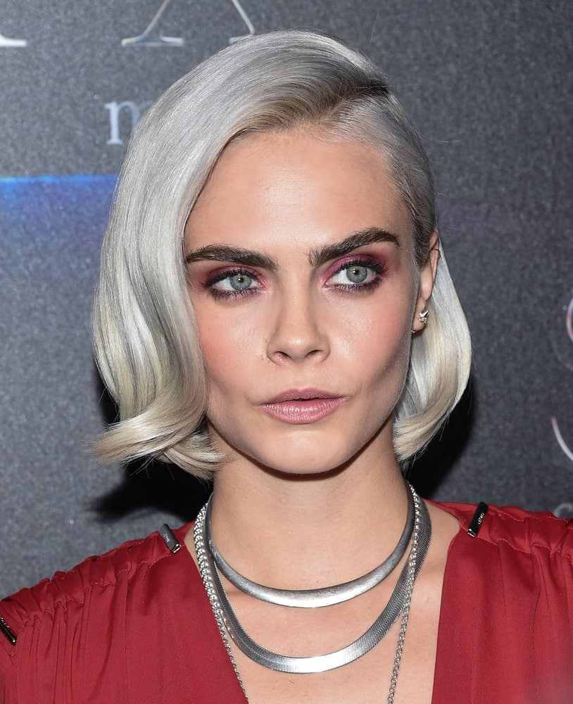 Supermodel, Cara Delevingne, is known for her bold brows; however, her ever-changing hairstyle also frequently puts her in the spotlight. Here, Delevingne has dyed her hair a shimmering silver-white and styled it with a deep slanting part and soft retro-style curls. The actress wore silver-colored jewelry to compliment her cool and classy hairstyle.