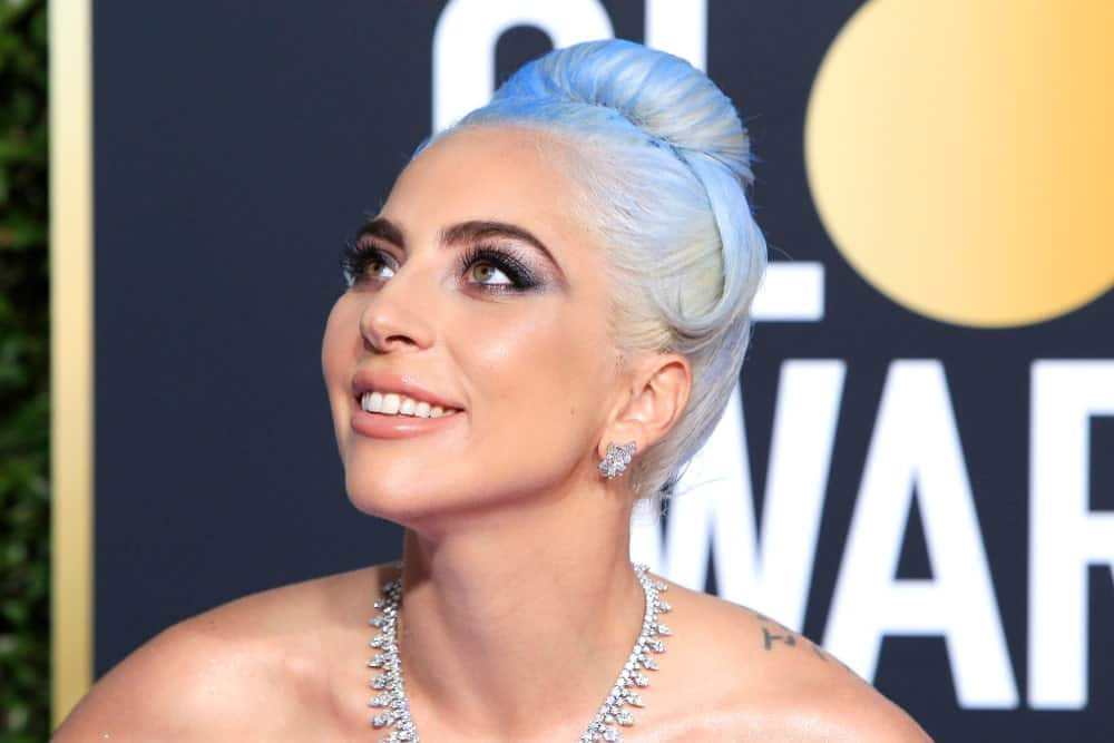 Here we see Lady Gaga sporting another stunning gray hairstyle for women. This look is achieved by pulling all her hair up into a high and tight bun before folding the tips forward and tucking them under themselves. One smooth strand has been left hanging at the side to complete this distinct chignon. Note that the top hair has been lightly sprayed with sky-blue hues for a fancier finish.