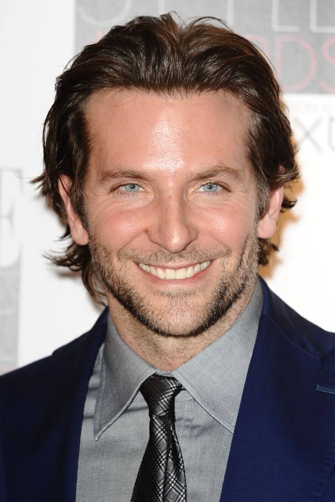 """Even though he is a phenomenal actor, one of Bradley Cooper's biggest claims-to-fame is his thick brown voluminous waves of hair. The """"A Star is Born"""" actor is one of the few Hollywood actors who sports shoulder-length hair and rocksit. On red carpet events, Cooper often styles his hair in a wet look by adding styling product to his wavy locks and pushing them back away from his forehead. The style further highlights the actor's prominent cheekbones and piercing eyes."""