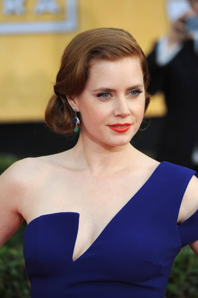 Worn by Amy Adams, this side-swept hairstyle for women comprises of a low side bun at the nape of her neck coupled with a well-defined swirl of hair at the front. This orderly hairstyle is suitable for numerous occasions including both, formal and casual events.