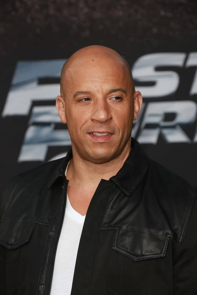 "If this isn't the ultimately classic shaved look, we don't know what is! Vin Diesel needs no introduction for he will be known as the guy with ""a slick bald head!"" He looks incredibly handsome here with his apparently naturally-balding head that gives him a kind of a 'likable tough guy' look. That very faint and barely visible facial hair just goes so well with the shave."