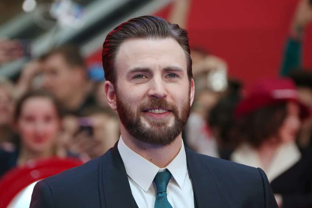 "Who doesn't love Captain America? Not only does he save the world, but he looks good doing it too. Chris Evans is known for his clean and polished look on the red carpet and this time isn't any different either. The ""Avengers"" actor chose to style his thick hair in a side-parted slicked back part. With his beautifully groomed beard, the actor looks very refined and dapper."