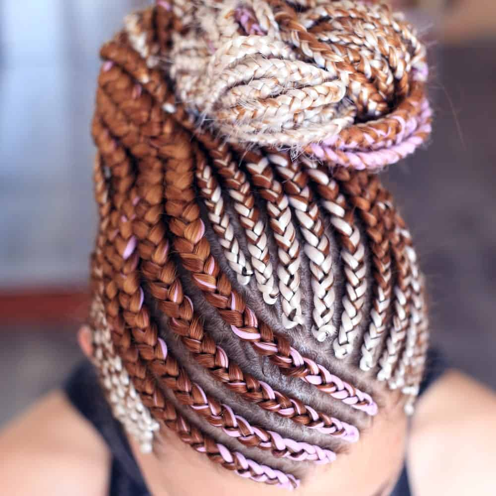 As the lady in the picture shows, you don't need to keep your long braids dangling all the time. She looped her long, dangling braids into a twisted bun onto the back and top of her head. To make the look even more dramatic, she incorporated brown-auburn, pale gold, and candy-pink threads into her hair to make her look stand out.