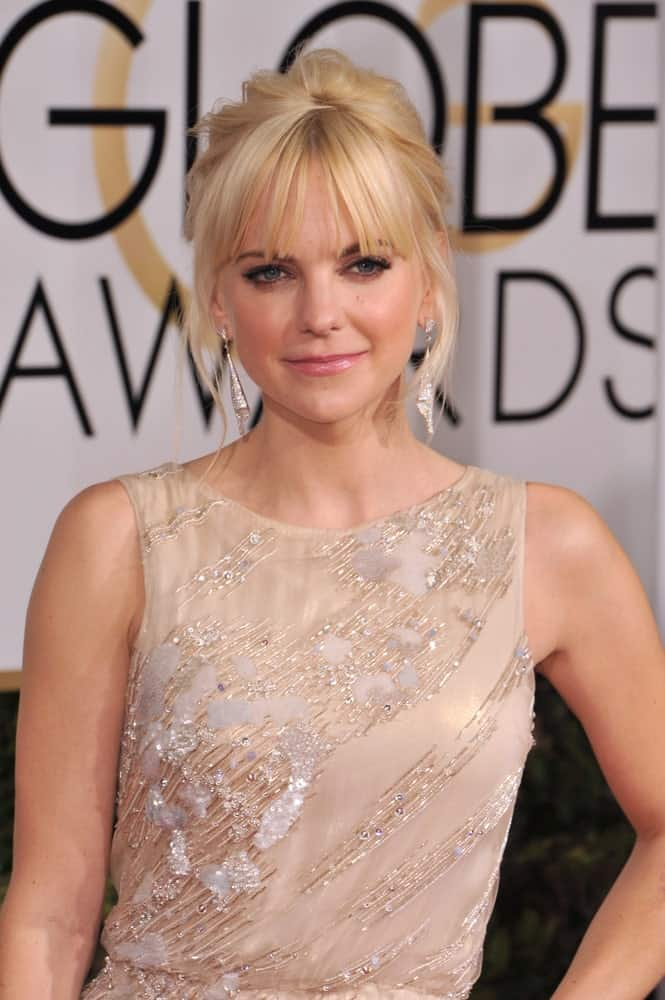 Anna Faris's elegant updo consists of blunt curtain-style bangs backed by a high chignon with some wavy tendrils at the side. This wedding-themed hairstyle will go well on other formal occasions as well.