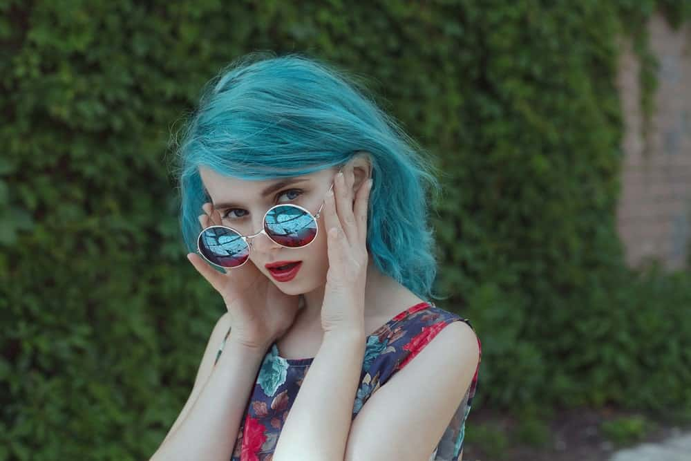 Woman with blue hair looking over her sunglasses.