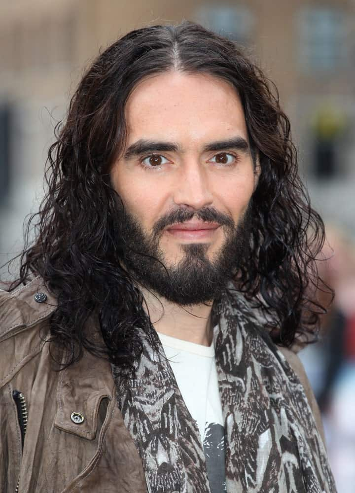 There is probably no one who rocks long curly hair better than Russell Brand! He has really long, curly black hair that falls on both sides of his face through a clean middle parting. The hair seems to have been gelled from the front since it is giving off a very wet, shiny look. The addition of the black beard and mustache further enhance the overall look and give him a very mature, macho look.