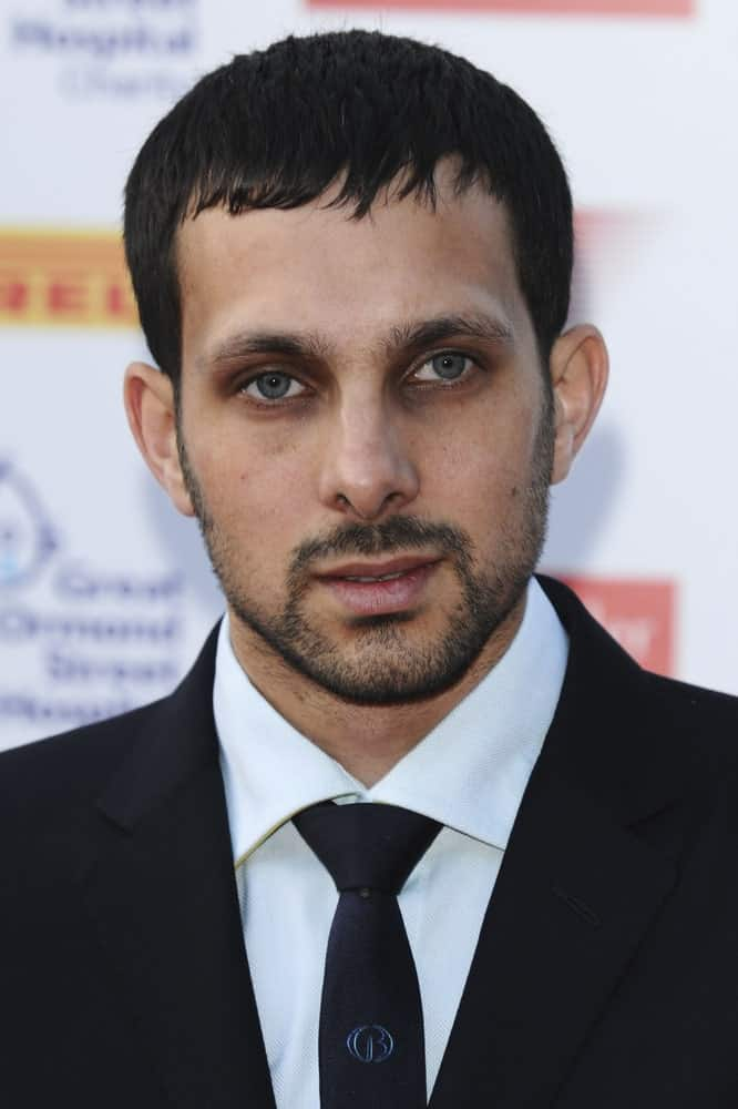 Taken at a lush party held in London, the picture shows Dynamo rocking a subtle fade haircut for men. His style combines a drop fade with a short chop which means that the hair at the sides of his head has been cropped to a short length while that at the top is left slightly longer and extends up to the forehead. The style is good for men looking for a really short haircut but not quite a buzzcut altogether.