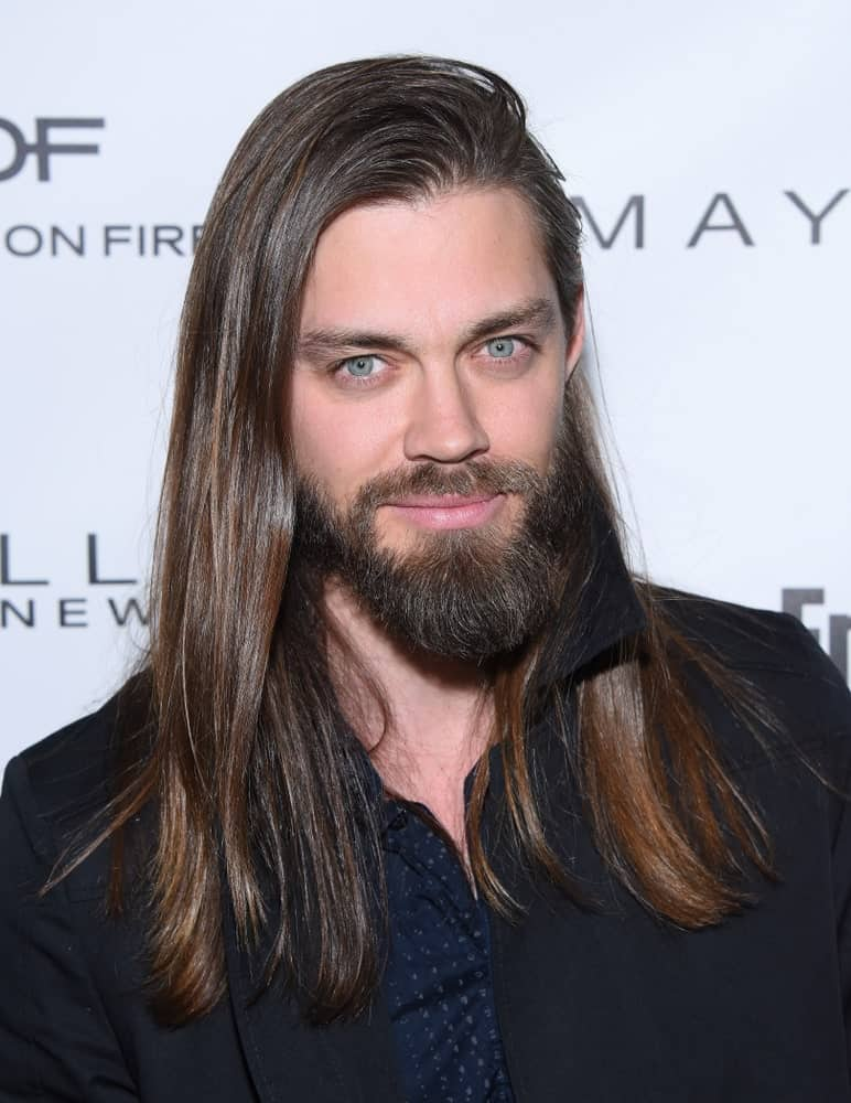 Tom Payne is another great name that you think of when it comes to men with long hair. He pulls off his super long and straight hair with absolute perfection, and it also suits him so well. His hair has been parted from the side that gives it a very voluminous look. The addition of the slightly long beard and mustache looks really classy with this hair making him look truly handsome.