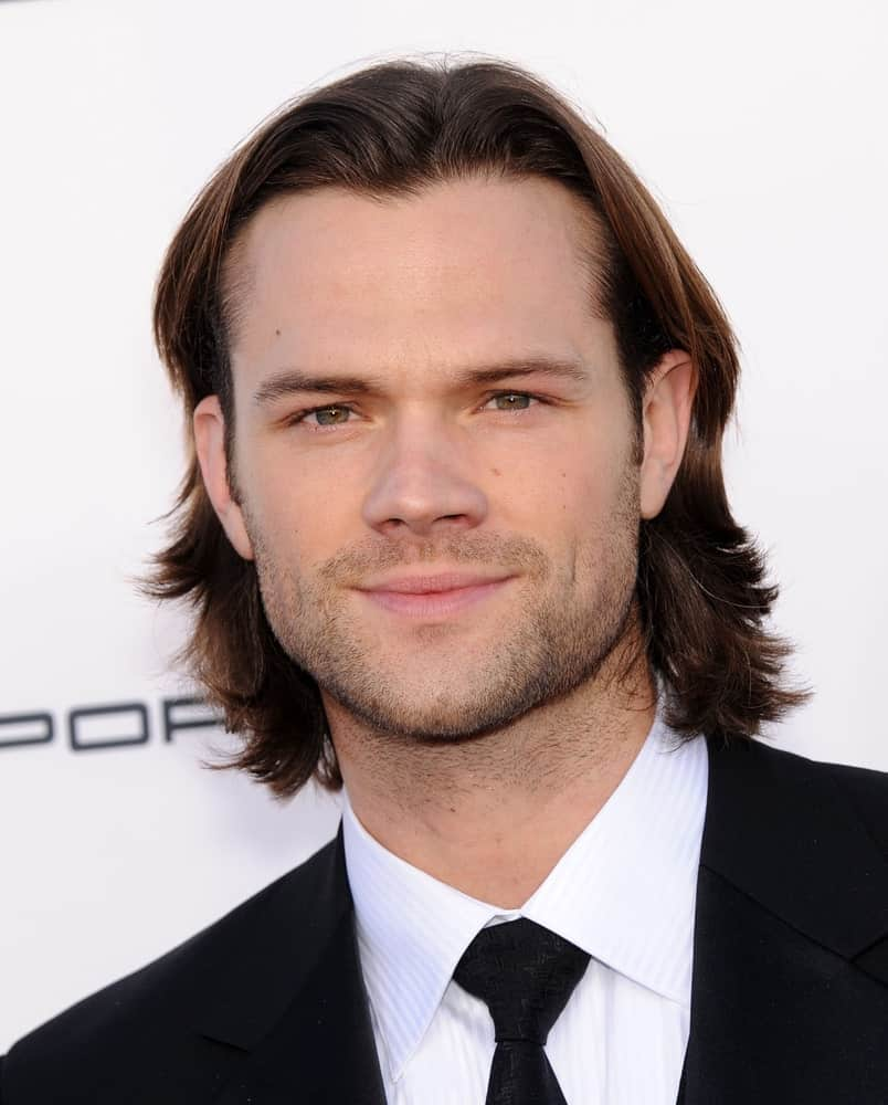 This hunk Jared Padalecki from the TV show Supernatural has a shag cut going on that looks just amazing on him. He has long hair that has been cut into wavy layers and has been parted down the middle. His brown layers gently rest on the sides of his face, and he has pinned them back behind his ears. He also has a really light beard that looks great with his long, chocolate brown hair.