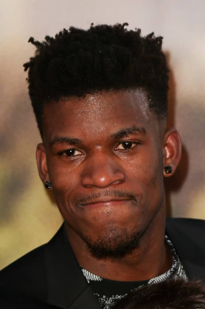 Men with coarse or extra curly hair need not despair because the NBA star, Jimmy Butler, provides a great hack to tackle those unruly locks – go for a fade haircut. Shaving off the edges, the player let the thick and coiled locks nest only above his head to achieve a fairly neat and manageable hairstyle. This fade with twisted locks clicked fellow sportsmen so much that almost half of the basketball league copied Butler's haircut.