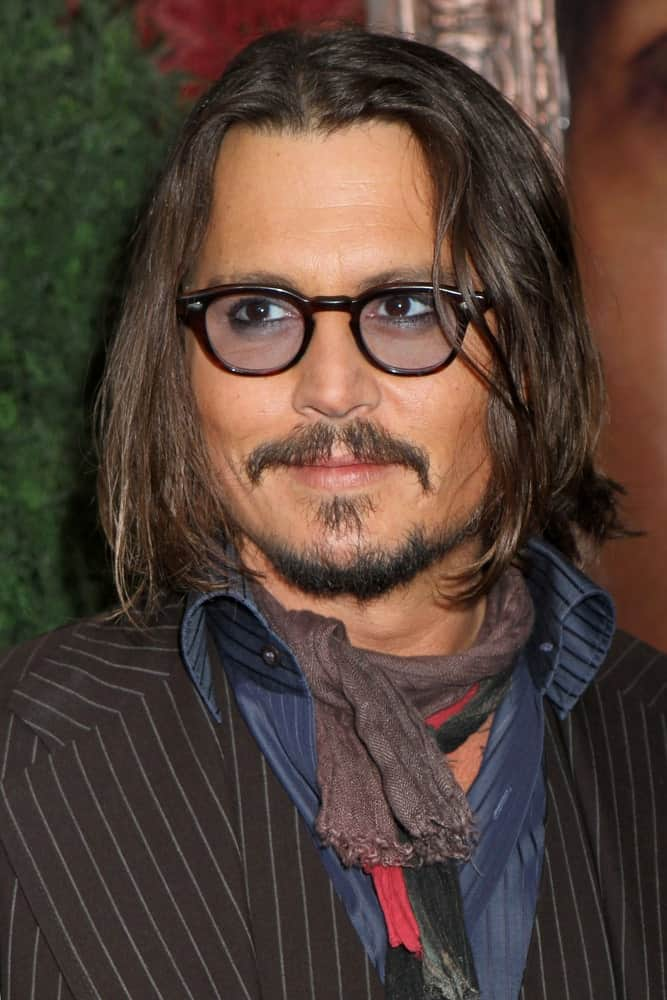 Looking for ways to jazz up your boring long hair? Perhaps you can take a leaf out of Johnny Depp's hair playbook. He has almost shoulder length hair with a middle parting that he has greatly accessorized with black, thick-rimmed tinted glasses. His beard style perfectly complements his long hair, making him look different and cool.