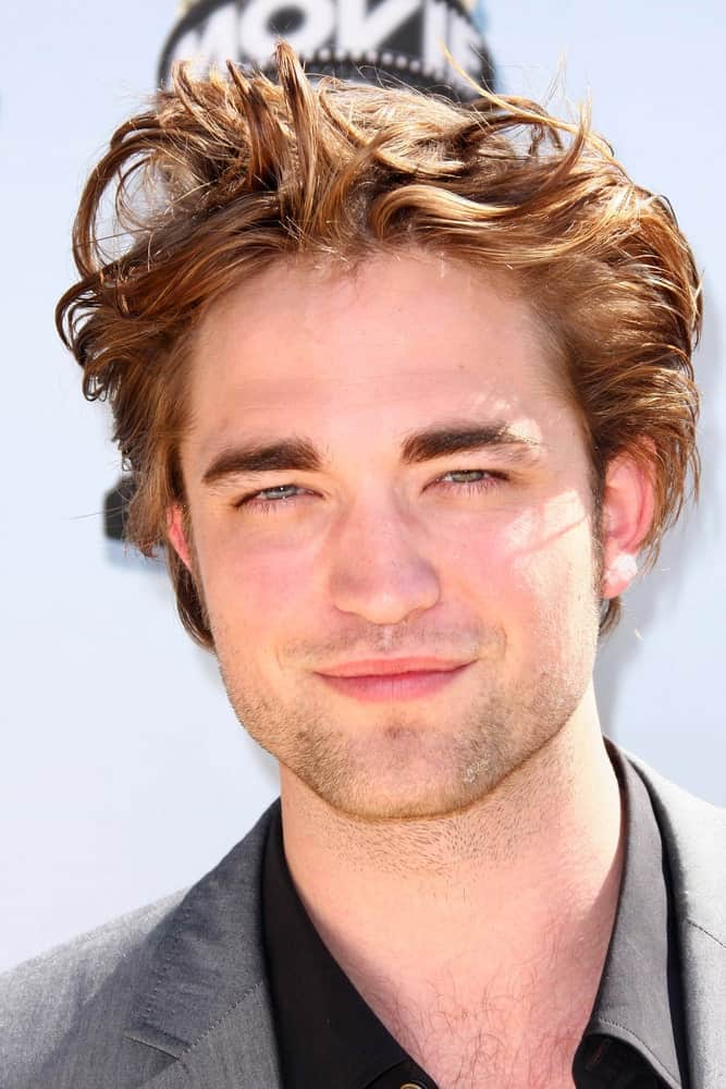 """After having played the character of """"Cedric Diggory"""" in the Harry Potter series, Robert Pattinson became quite the eye candy for most girls with his perfectly gorgeous looks and his honey-toned hair. He looks like a dream come true with his slightly wavy hair that have been dyed a beautiful caramel blonde color. His highlights seem to be sparkling in the sun and emit quite a radiant, shiny glow."""