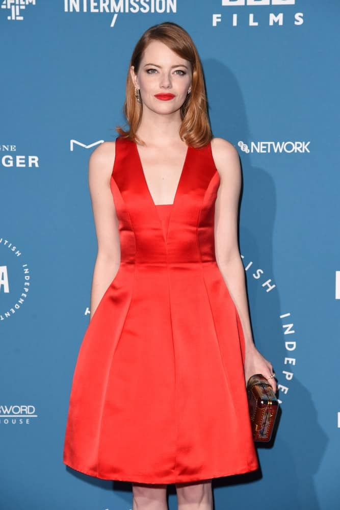 On December 02, 2018, Emma Stone paired her gorgeous red cocktail dress with bold red lips and a straight side-swept hairstyle with slight waves at the tips at the British Independent Film Awards 2018 at Old Billingsgate, London.