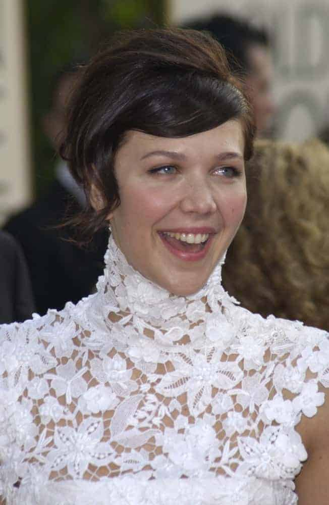 Maggie Gyllenhaal was at the Golden Globe Awards at the Beverly Hills Hilton Hotel on January 19, 2003. She paired her lovely white dress with a short brunette side-swept hairstyle.