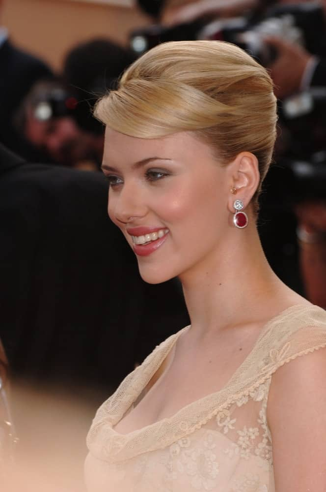 Actress Scarlett Johansson was at the screening of Woody Allen's Match Point at the 58th Annual Film Festival de Cannes on May 12, 2005, in Cannes, France. She wore a stunning sheer dress to match her slick and neat upstyle incorporated with side-swept bangs.