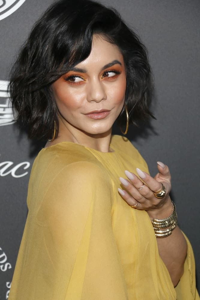 Vanessa Hudgens' charming yellow sheer dress went quite well with her tousled short bob hairstyle with side-swept bangs at the Art Of Elysium's 11th Annual Heaven Celebration held at the Barker Hangar in Santa Monica, USA on January 6, 2018.