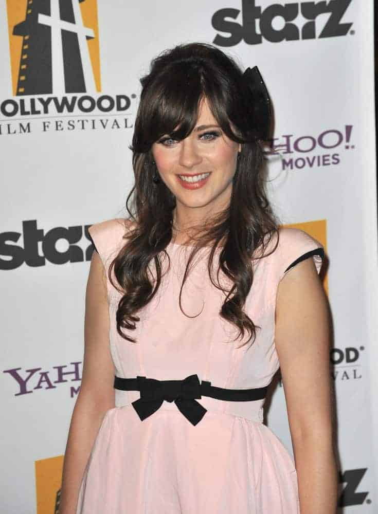 On October 26, 2009, Zooey Deschanel was at the 13th Annual Hollywood Awards at the Beverly Hilton Hotel. She wore a lovely pink dress with her long and loose raven wavy hairstyle with side-swept bangs and a ribbon.