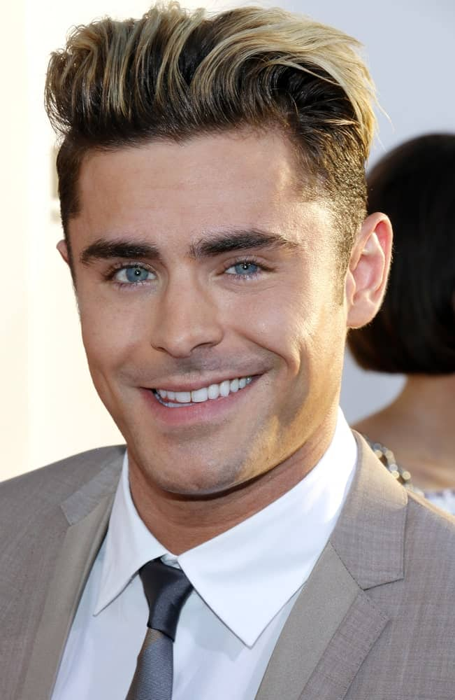 This is like a mixture or a hybrid version of a disconnected undercut, slicked back undercut as well as a pompadour undercut. All three different styles are merged into one that perhaps only someone like Zac Efron can pull off with such elegance and perfection. He is looking utterly dashing in this look where he has channeled the 1950s in his hair with the addition of the unique pompadour. It seems to be working really well with his long locks and has brought forth quite a slick and a stylish look. That million-dollar smile and those ice-blue eyes further enhance it, making him look all the more gorgeous!
