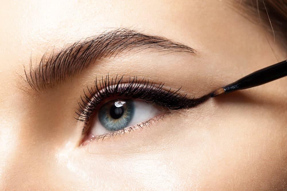 Woman applying eyeliner.