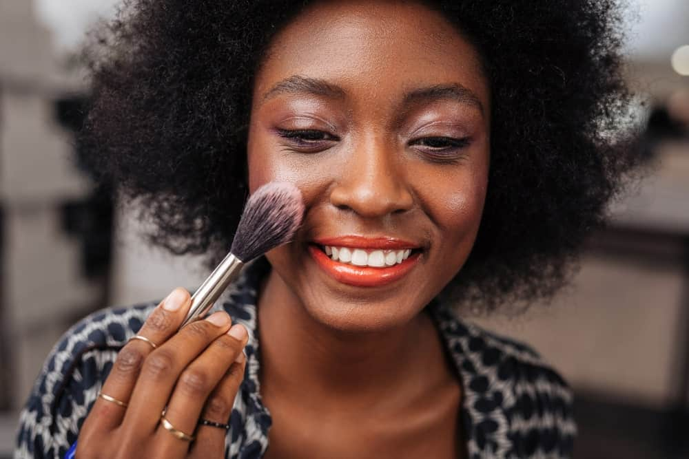 Woman applying rogue or blush.