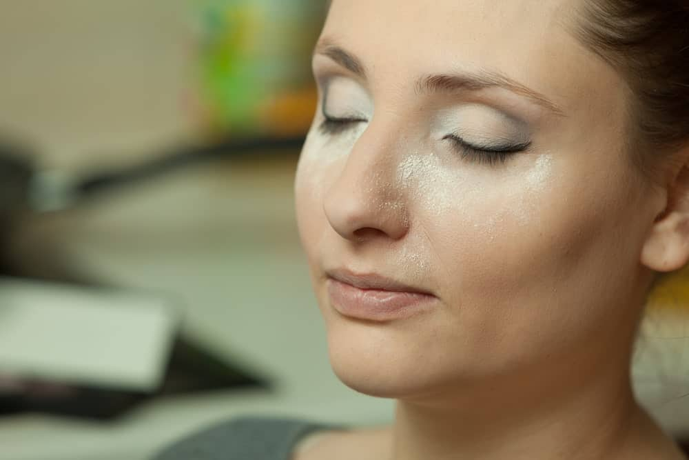 Woman with setting powder on her face.