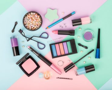 Several makeup products on a multicolored background