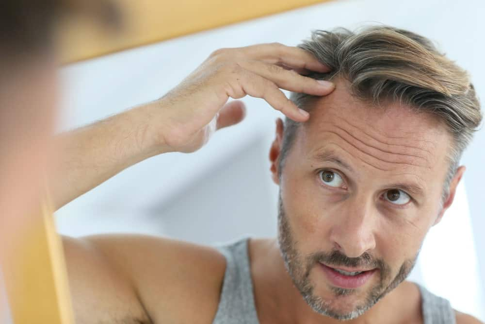 Middle-aged man worrying about his ageing hair.
