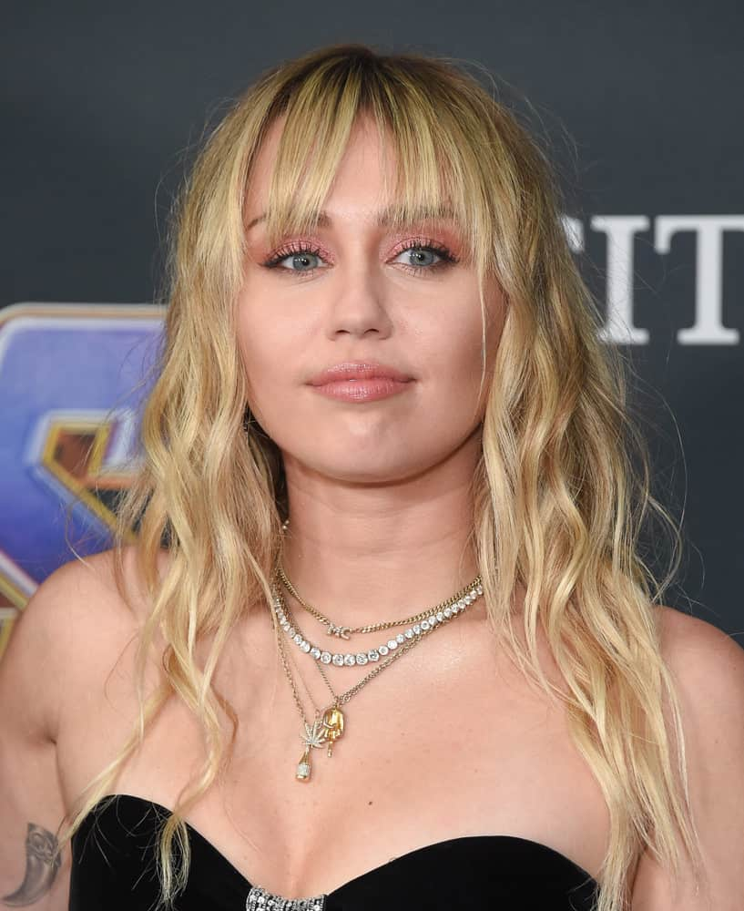 Miley Cyrus with Long wavy blonde hair with bangs