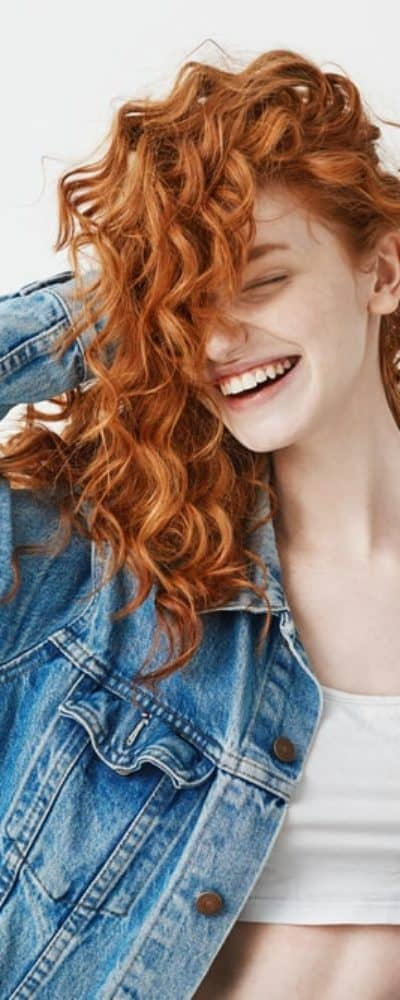 A red-haired girl smiles and touches her curls on a white background