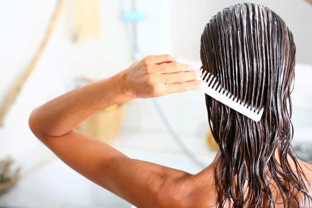 A woman applying hair conditioner to her wet hair