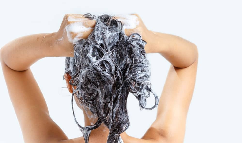 Woman applying shampoo